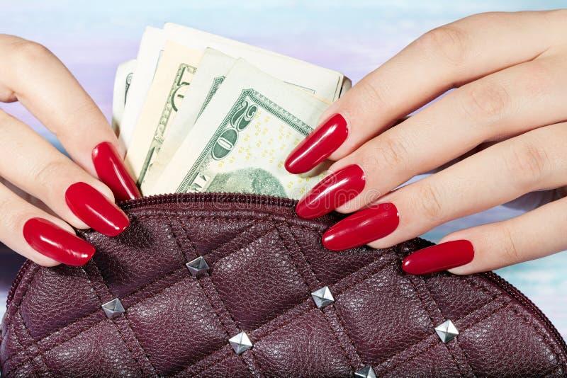 De handen met lang manicured spijkers die geld van de handtas nemen stock fotografie