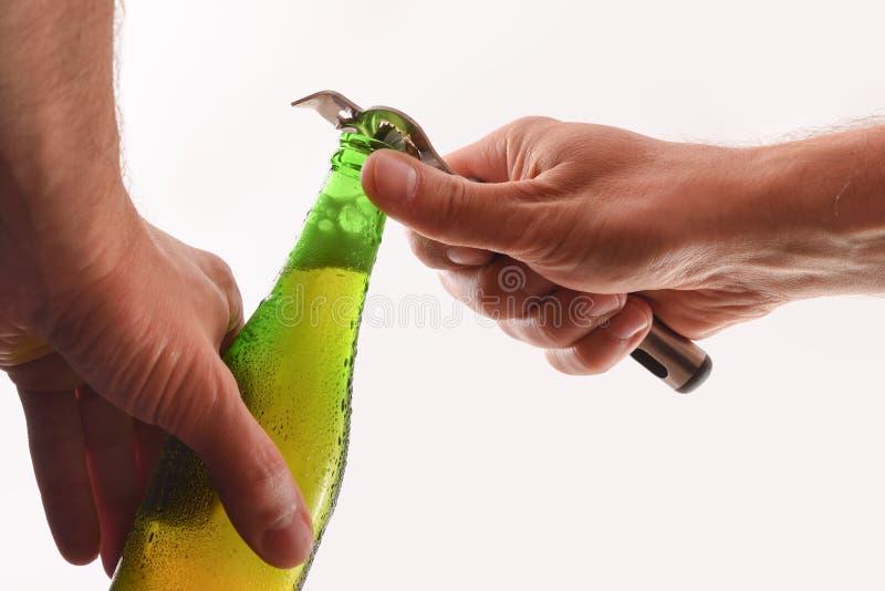 De handen openen een bier kunnen met flesopener geïsoleerd wit stock afbeeldingen