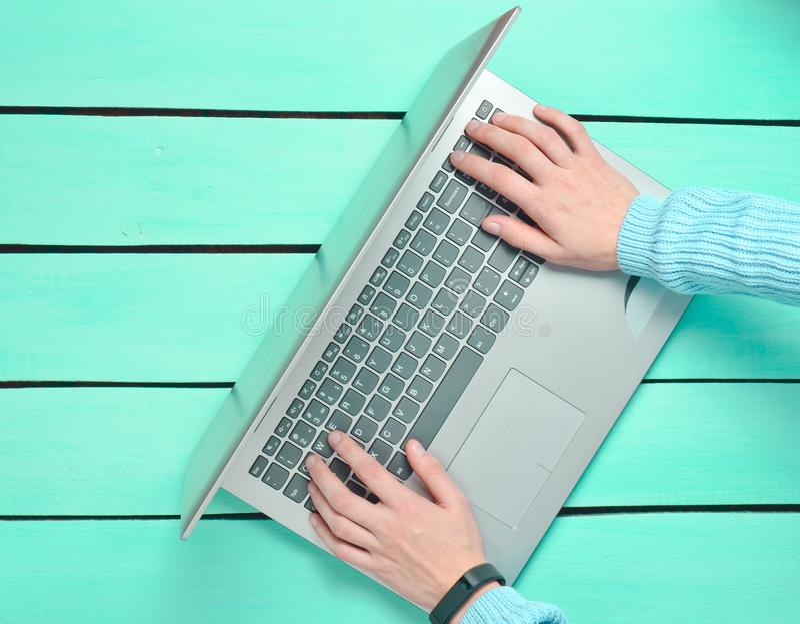 De handen typen op het laptop toetsenbord op een blauwe houten lijst Het concept het freelancing, het werk op Internet Hoogste me stock foto