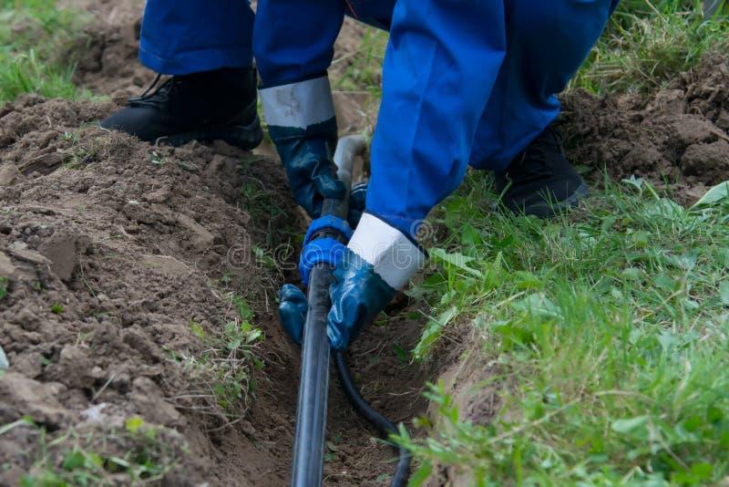 De handen van de arbeider, in blauwe handschoenen, legden een plastic pijpleiding in een open geul in de grond royalty-vrije stock afbeeldingen