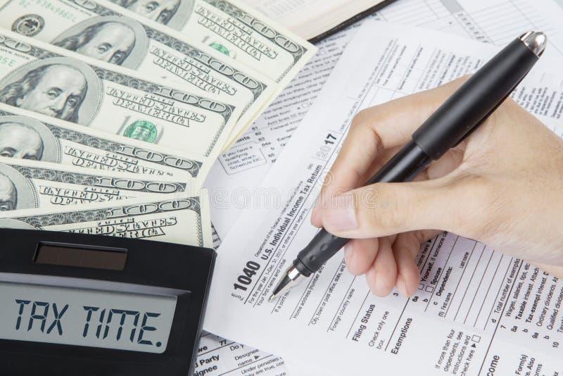 De handen van arbeider schrijft op een belastingsvorm stock foto's