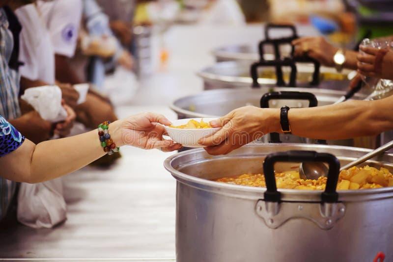 De handen van de armen ontvangen voedsel van de handen van de filantroop: concept het geven royalty-vrije stock foto