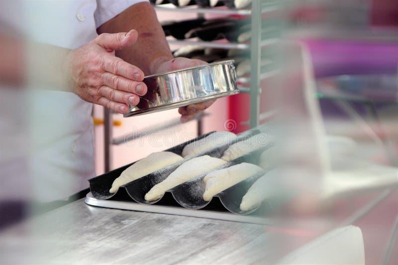 De handen van Baker bestrooien bakselbloem, alvorens het in de oven te maken stock afbeelding