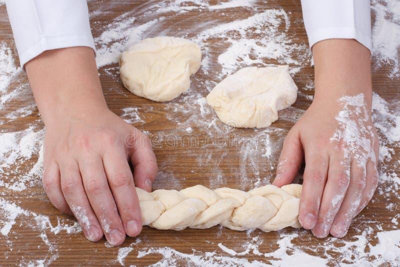 De handen van Baker weven brooddeeg. royalty-vrije stock afbeeldingen