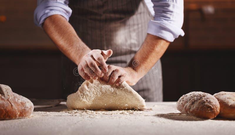 De handen van bakkers` s mannetje kneden deeg royalty-vrije stock foto's