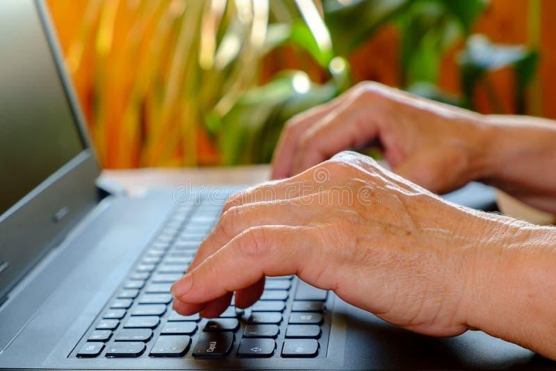 De handen van bejaarden typt tekst op laptop close-up stock foto's