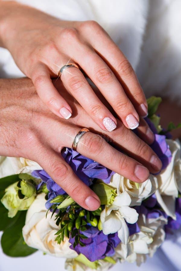 De handen van de bruid en de bruidegom liggen op een boeket van bloemen De mening vanaf de bovenkant Huwelijk royalty-vrije stock afbeeldingen
