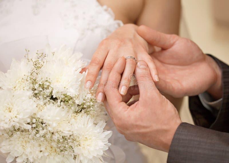De handen van bruidegom en bruid met ring sluiten omhoog stock afbeelding