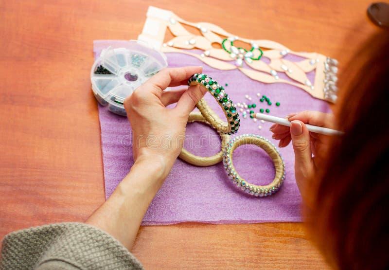 De handen van de close-upvrouw, die armbanden met kleurrijke glanzende bergkristallen verfraaien royalty-vrije stock foto's