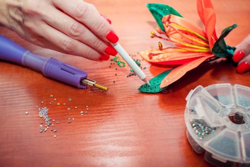 De handen van de close-upvrouw, die kunstmatige leliebloem met kleurrijke glanzende bergkristallen verfraaien stock fotografie