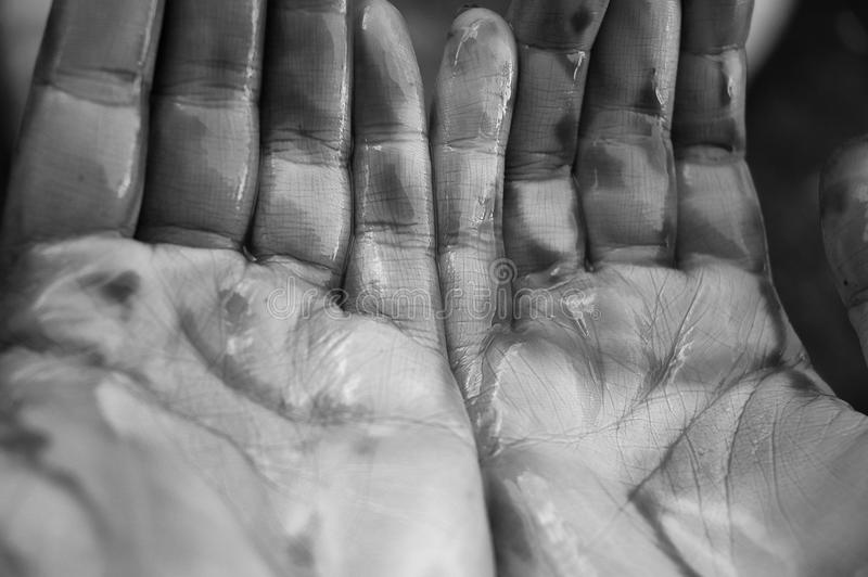 De handen van de arbeider na het schoonmaken van kust van oliemorserij stock afbeelding