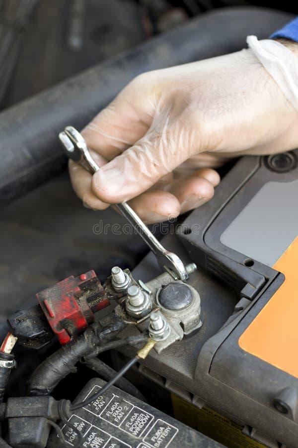 De handen van de autowerktuigkundige in beschikbare handschoenen schroeven de batterijkoppeling los stock fotografie