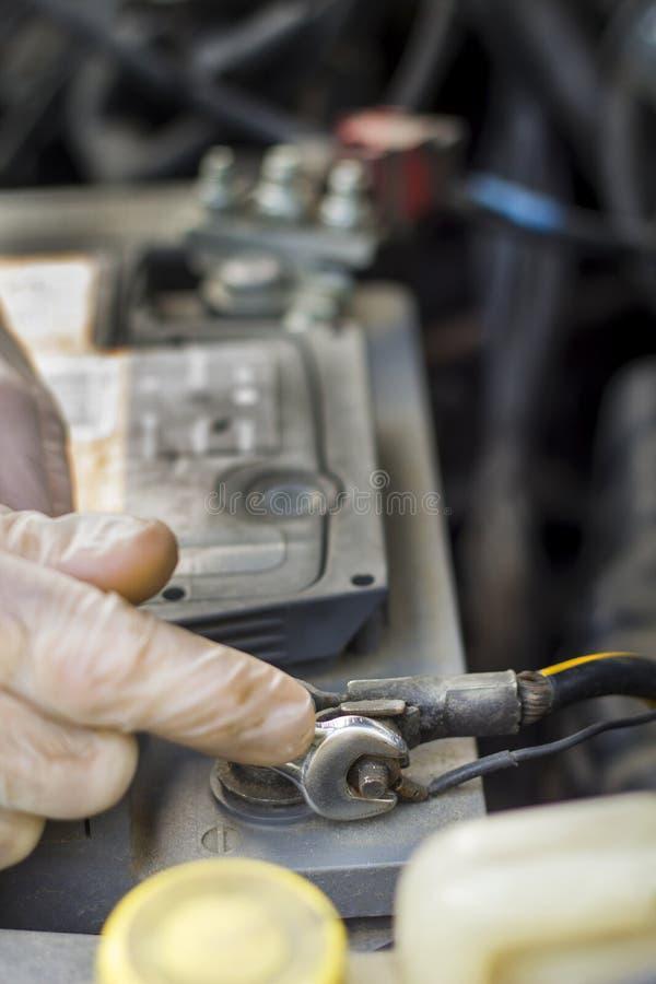 De handen van de autowerktuigkundige in beschikbare handschoenen schroeven de batterijkoppeling los stock foto's