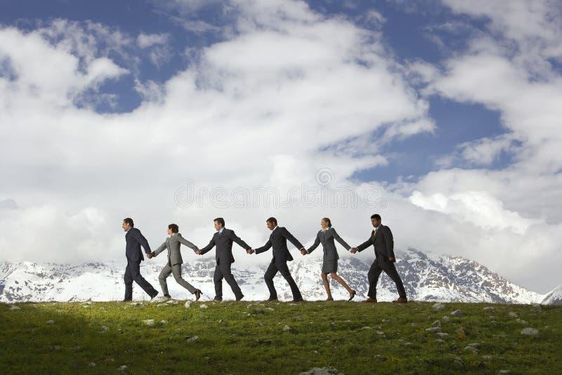 De Handen van de bedrijfsmensenholding en het Lopen door Bergen stock foto