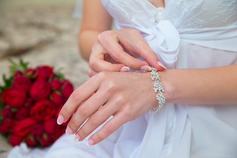 De handen van de bruid met de armband Huwelijksboeket in backgrou stock fotografie