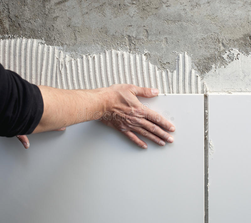 De handen van de de metselaarmens van de bouw op tegels werken royalty-vrije stock foto's