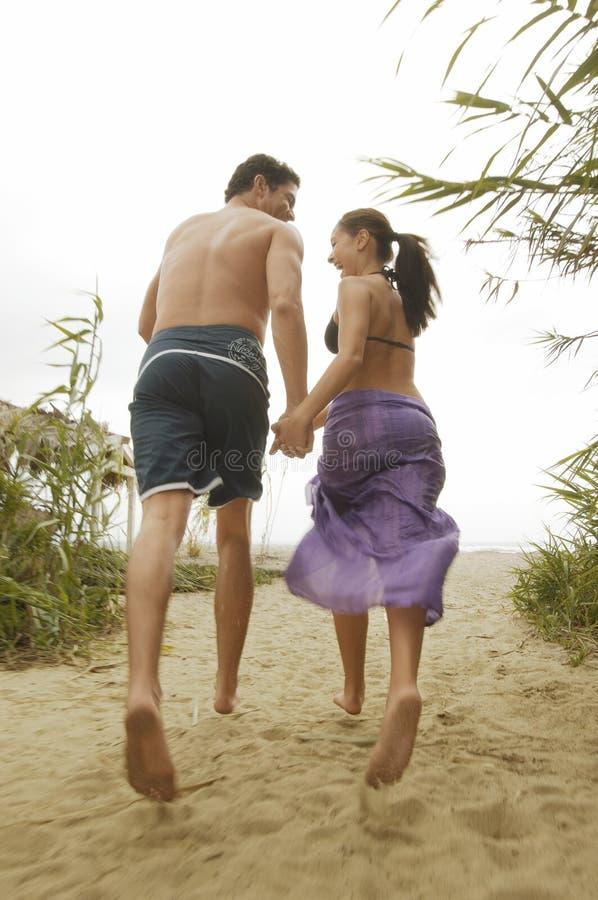 De Handen van de Holding van het paar, die op Strand lopen stock afbeeldingen