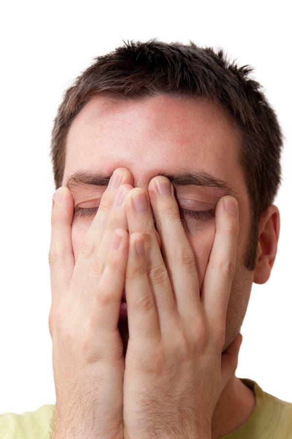 De handen van de jonge mensenholding op zijn gezicht stock afbeeldingen