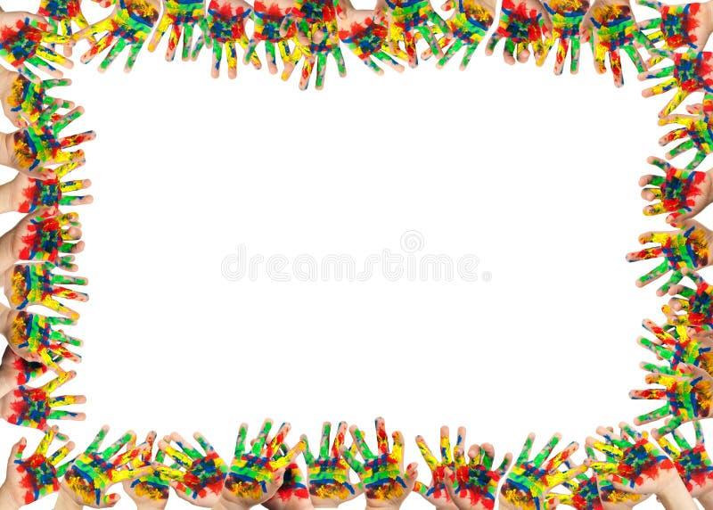 De handen van de jongen met kleurrijke verf worden geschilderd die stock fotografie