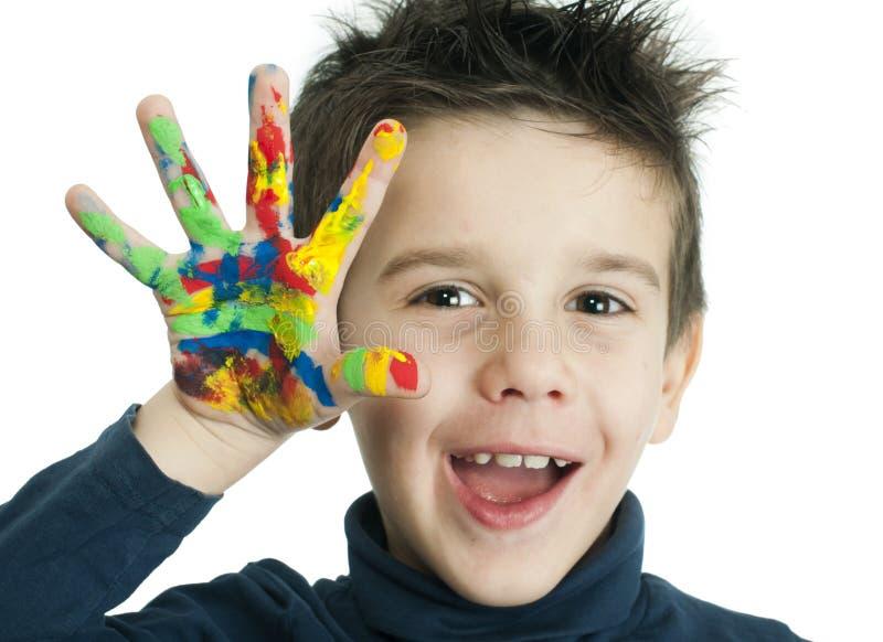 De handen van de jongen met kleurrijke verf worden geschilderd die stock foto