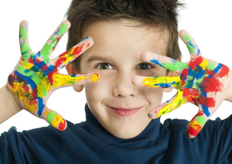 De handen van de jongen met kleurrijke verf worden geschilderd die stock afbeelding
