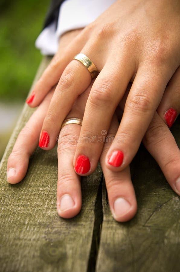 De handen van de jonggehuwde met ringen stock foto