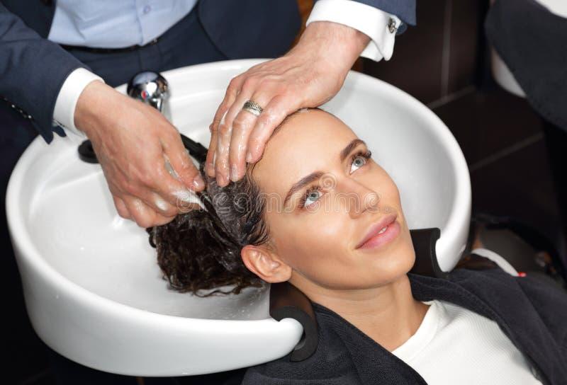 De handen van de kapper wassen het hoofd van een meisje royalty-vrije stock fotografie