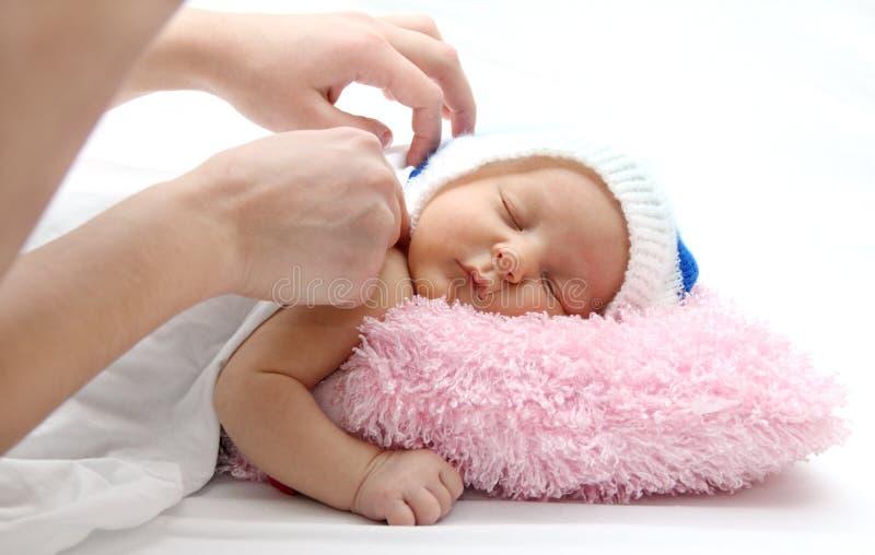 De handen van de moeder en slaapbaby stock foto's