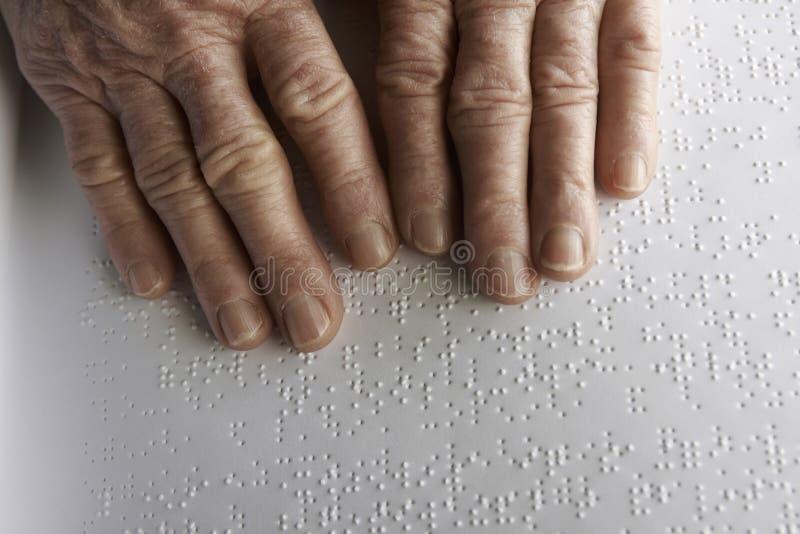 De handen van de oude vrouw, die een boek met braille-taal lezen stock afbeeldingen