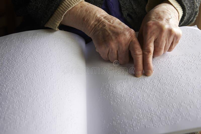 De handen van de oude vrouw, die een boek met braille-taal lezen royalty-vrije stock afbeelding