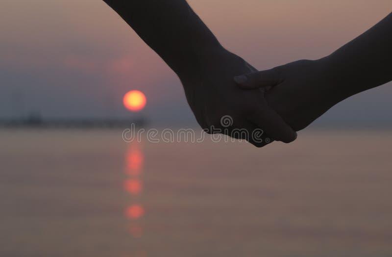 De handen van de paarholding bij zonsondergang stock afbeelding