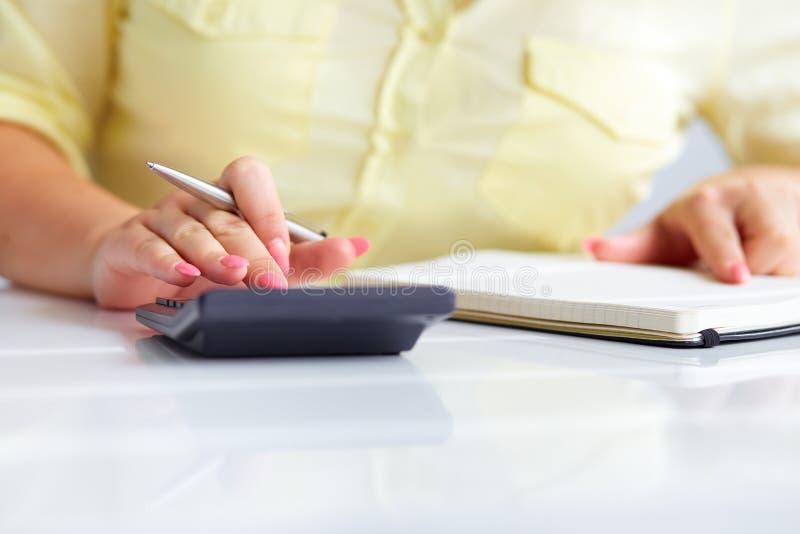De handen van de vrouw met een calculator royalty-vrije stock afbeelding
