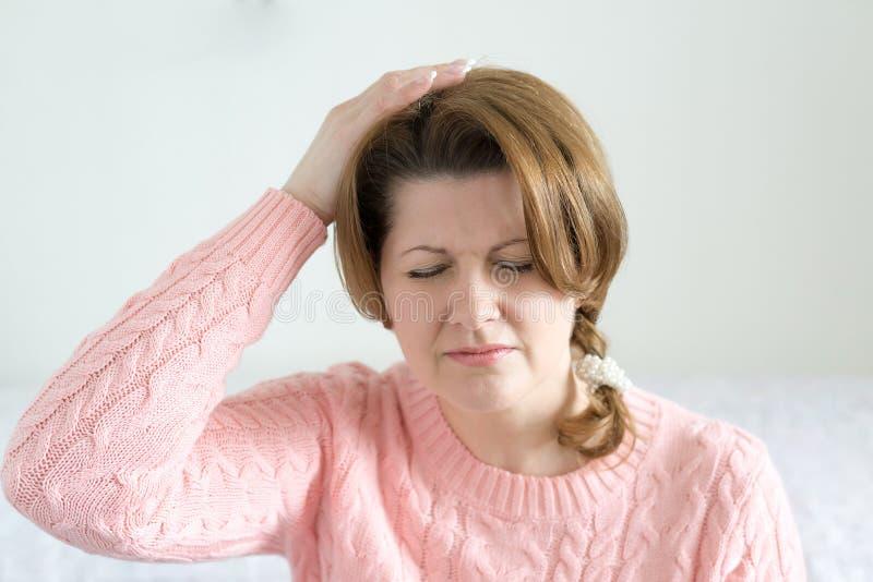 De handen van de vrouwenholding op hoofd, depressie, pijn, migraine stock fotografie