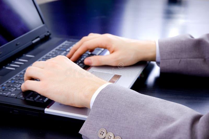 De handen van de zakenman op notitieboekjetoetsenbord stock foto
