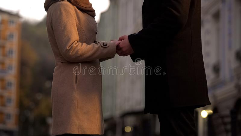 De handen van de echtpaarholding teder, nog in liefde, romantische gang in grote stad stock foto's