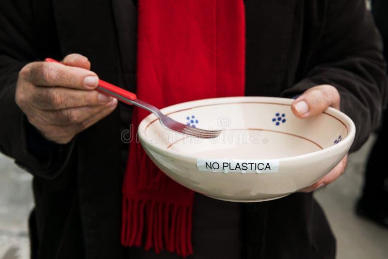 De handen van een bejaarde Italiaanse activist houden een plaat met de inschrijving geen plastiek concept nul afval en geen plast royalty-vrije stock foto's