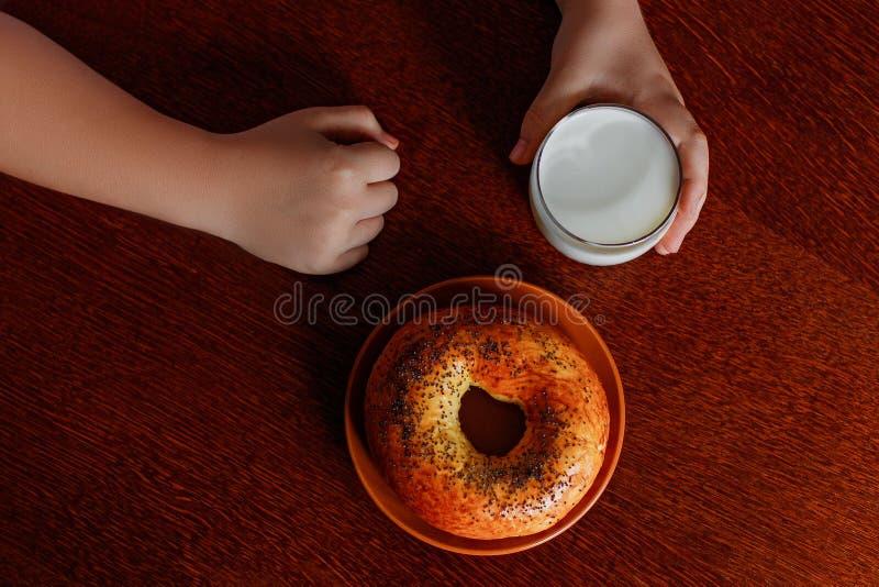 In de handen van een glas verse melk en een ongezuurd broodje op de lijst royalty-vrije stock fotografie