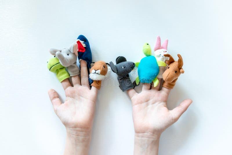 De handen van een kind met handpoppen, speelgoed, poppen sluiten omhoog op witte achtergrond - het spelen marionettentheater en k royalty-vrije stock foto