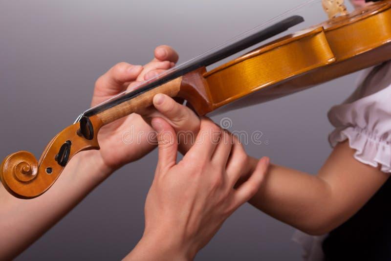 De handen van een leraar van het spelen viool verbeteren weinig leerling op een grijze achtergrond stock fotografie