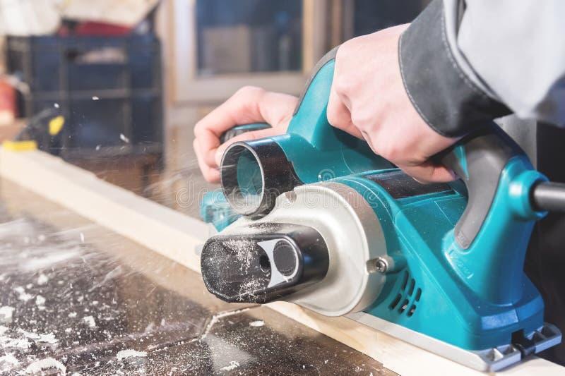 De handen van een machtshulpmiddelen van de timmermans werkende houtbewerking Sluit omhoog van het werk van elektrische planer stock foto's