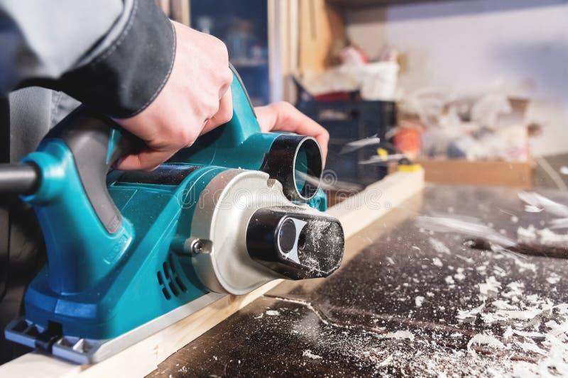 De handen van een machtshulpmiddelen van de timmermans werkende houtbewerking Sluit omhoog van het werk van elektrische planer royalty-vrije stock foto's