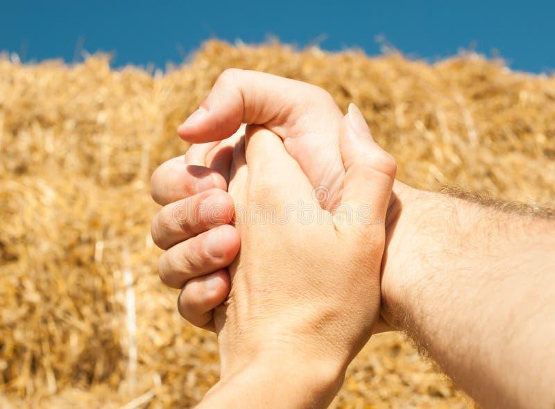 De handen van een man en een vrouw zijn samen geweven tegen een achtergrond van stro en een blauwe hemel in de zomer stock foto's