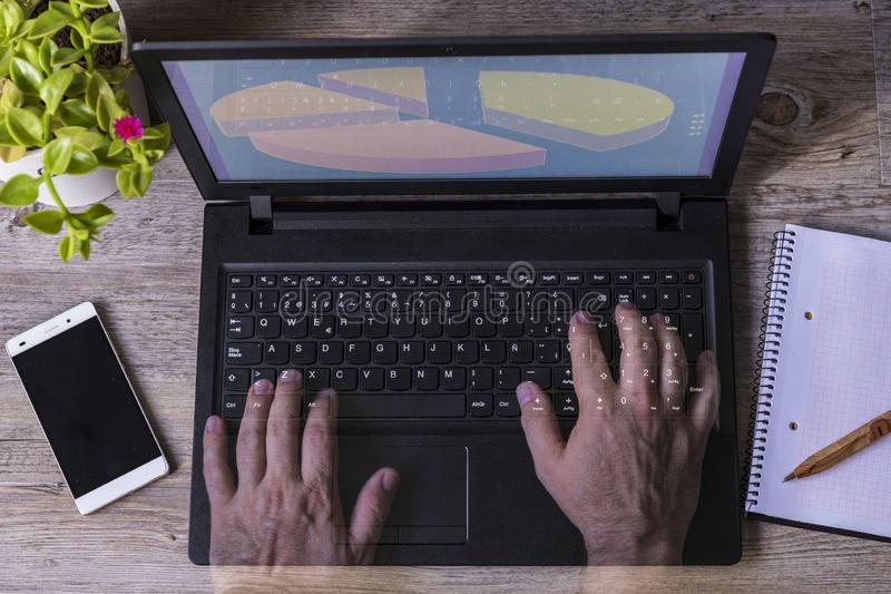 De handen van een mens in het notitieboekje van de computertelefoon planten houten lijst royalty-vrije stock foto