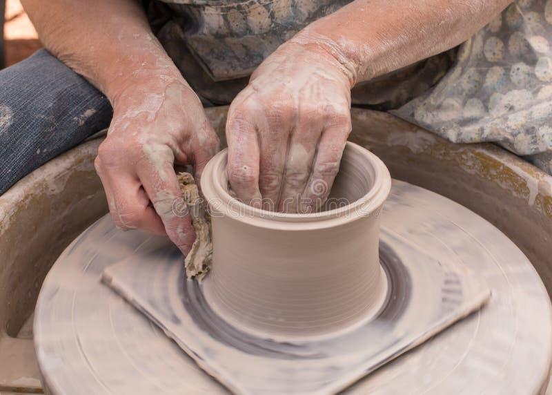 De handen van een pottenbakker die de klei op een het werpen wiel vormen stock foto