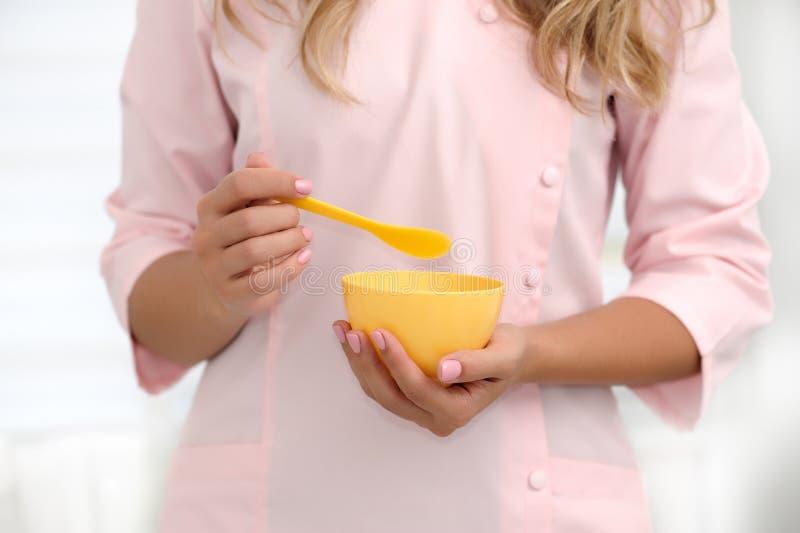 De handen van een schoonheidsspecialist bewegen de ingrediënten in een gele kop voor het toepassen van het masker op de huid De k royalty-vrije stock afbeeldingen