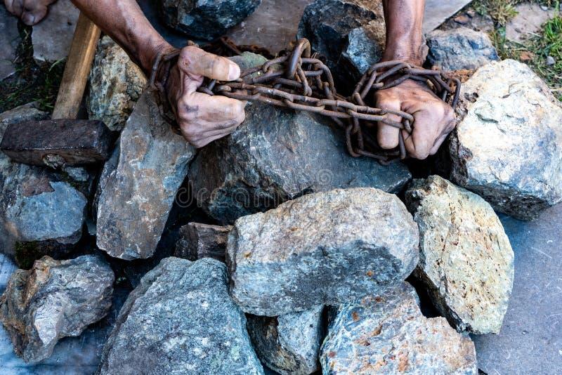 De handen van een slaaf in een poging te bevrijden Het symbool van slavenarbeid Dient kettingen in stock fotografie