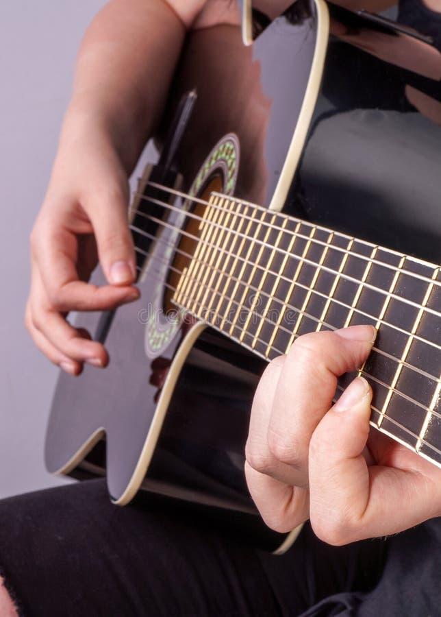 De handen van een tiener speelt gitaar royalty-vrije stock afbeelding