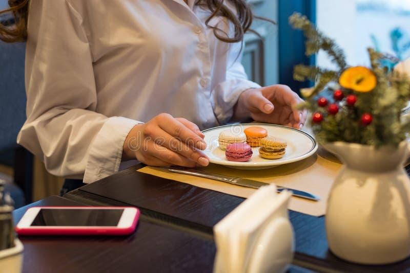 De handen van een vrouw die bij een lijst met een kop thee en makarons in een koffie zit stock foto