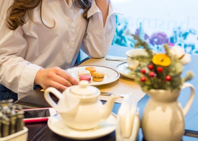 De handen van een vrouw die bij een lijst met een kop thee en makarons in een koffie zit royalty-vrije stock foto