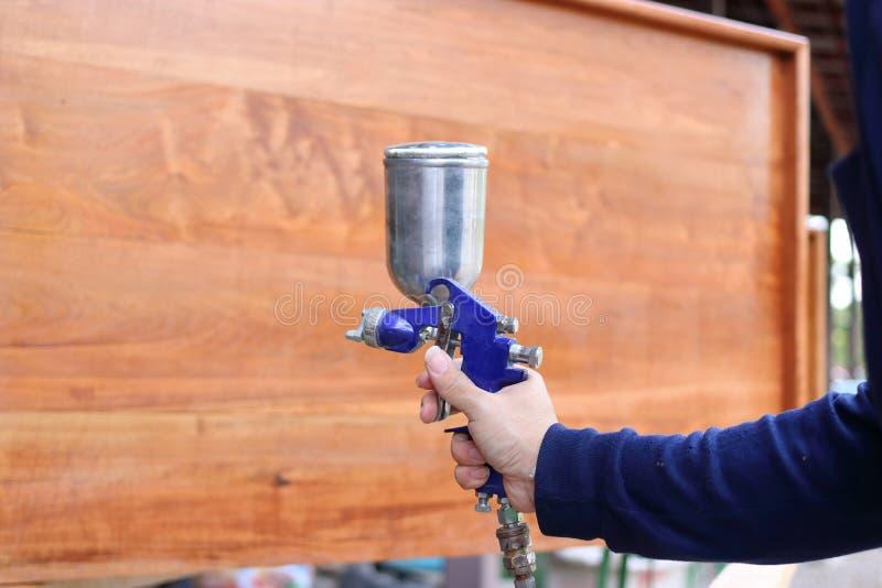 De handen van fabrieksarbeider die nevel toepassen schilderen kanon met een houten meubilair de workshopachtergrond royalty-vrije stock fotografie